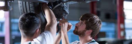 Two car mechanics are repairing a car