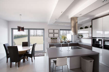 chandelier: Modern and light kitchen with dining room Stock Photo