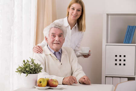 elder care: Beauty granddaughter serving grandfather cup of coffee