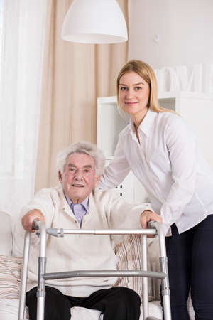 nursing treatment: Disabled man using walking frame and assisted carer Stock Photo