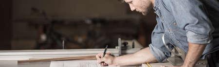 menuisier: Jeune menuisier est en train d'écrire quelque chose sur son plan Banque d'images