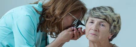 otoscope: Doctor is checking elder lady ear with otoscope
