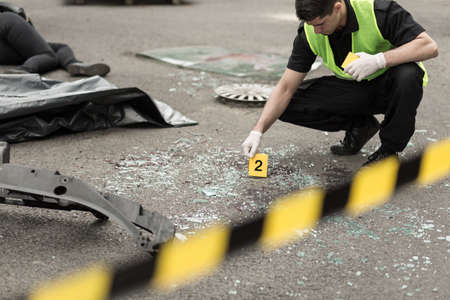 car wreck: Policeman during investigation at road accident area Stock Photo
