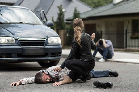 Bloody victim of car accident lying on the street Stockfoto