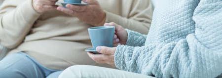 Twee vrouwen die gesprek en koffie drinken