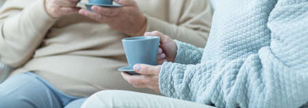 retirement age: Two women having conversation and drinking coffee