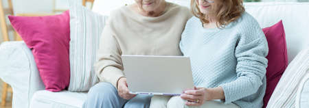 looking at computer: Carer is showing elder lady how to use computer