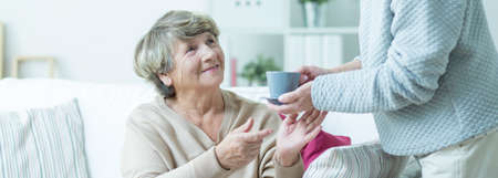 persona mayor: Cuidador está dando taza de té para mujer de edad avanzada