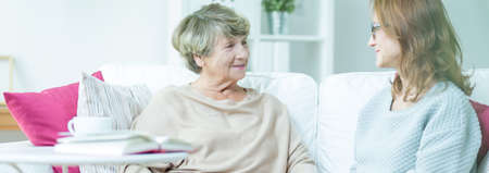 polite: Two women are having polite conversation on couch Stock Photo
