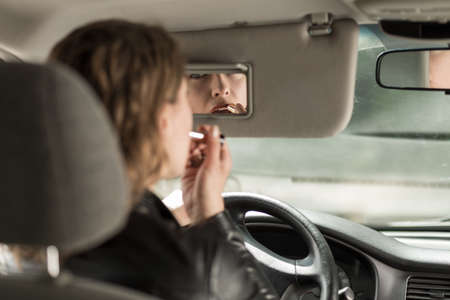 female driver: Young female driver applying lipstick in car Stock Photo