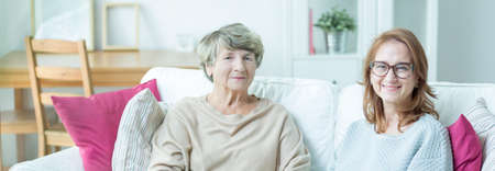 carer: Elder lady with carer sitting on a couch