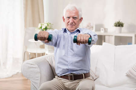 old sofa: Senior man exercising with dumbbells at home