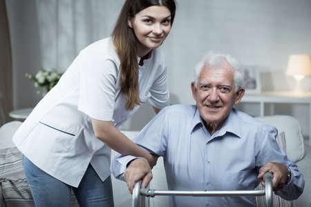 Verpleegkundige helpt gehandicapte senior man met staande Stockfoto