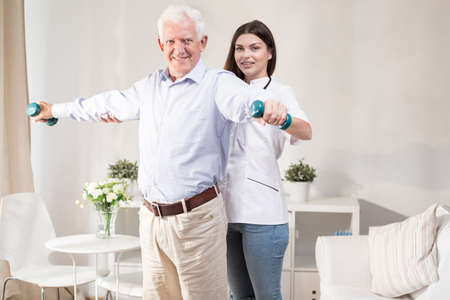 physical therapist: Senior man training with dumbbells during home physiotherapy
