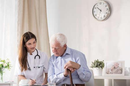 consulta médica: Doctor que habla con el hombre mayor sobre su enfermedad Foto de archivo