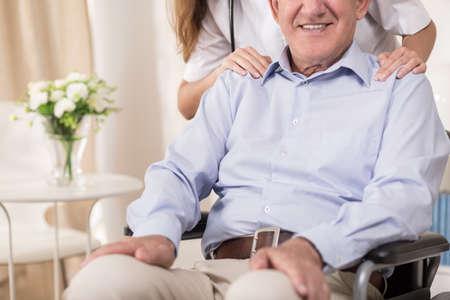 Gehandicapte senior man zit in een rolstoel