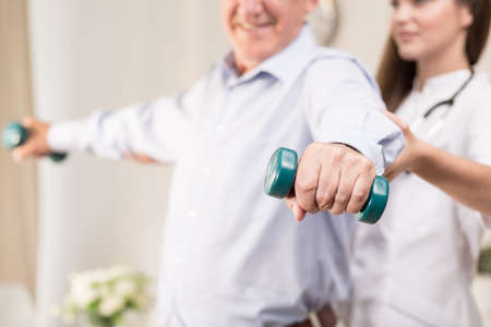 retiree: Retiree training with dumbbells assisted by young physiotherapist