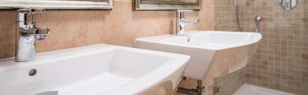 washbasins: Ceramic washbasins in caramel tiled modern bathroom Stock Photo