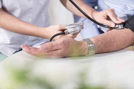 hipertension: Primer plano de cardiólogo femenina medir la presión arterial