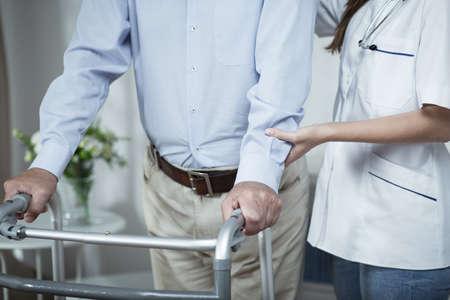 Gehandicapte man met behulp van rollator tijdens de revalidatie Stockfoto
