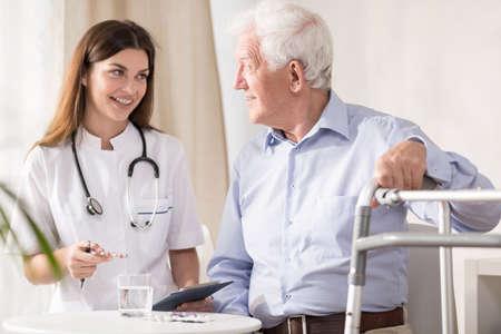 marcheur: Docteur visite patient plus âgé handicapé à la maison