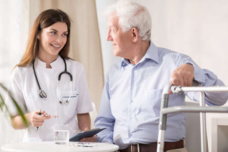 consulting room: Doctor visiting disabled senior patient at home Stock Photo