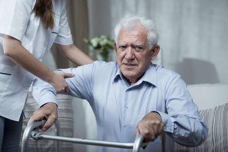 Fisioterapista aiutare disabile uomo anziano con in piedi Archivio Fotografico - 43066070