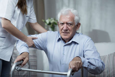Physiotherapist helping disabled senior man with standing