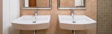 washbasins: Two basins in caramel tiled contemporary restroom