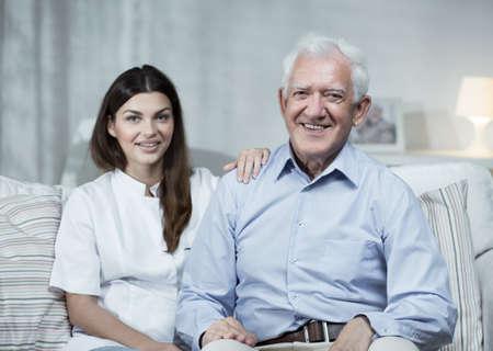 hombres trabajando: Enfermera y hombre mayor sentado en el sofá Foto de archivo