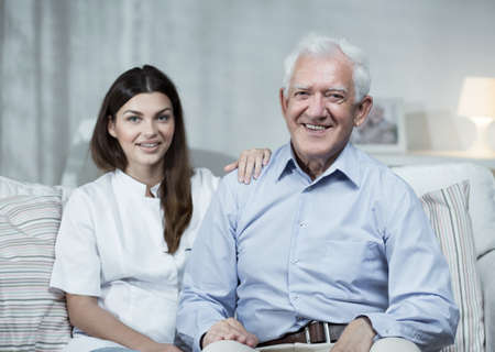 old carer: Nurse and senior man sitting on the sofa