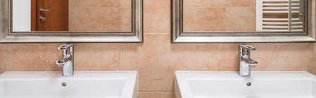 washbasins: Two ceramic washbasins with framed mirrors above Stock Photo