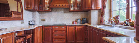 Wooden cupboards in kitchen in traditional style