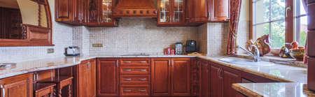 casa colonial: Armarios de madera en la cocina de estilo tradicional