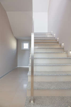 commodious: Marble stairs with steel handrail in minimalist storey house