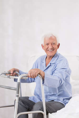 old man sitting: Photo of happy patient after operation with zimmer