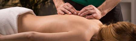 columna vertebral: mujer que tiene un tratamiento Joven acupresión para el dolor de espalda