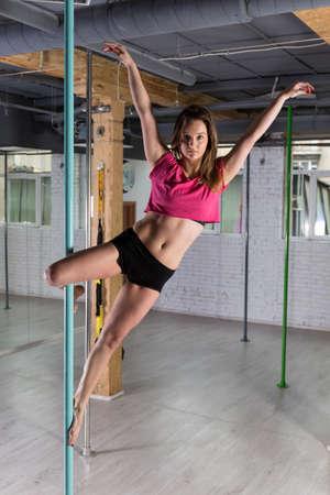 during: Young woman posing during pole dance training Stock Photo
