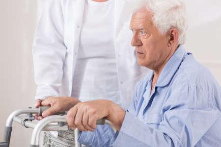 personas ayudando: Cierre de paciente mayor triste con problemas para caminar Foto de archivo