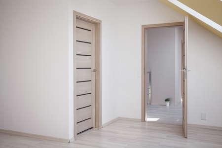 abrir puerta: Vaciar habitaci�n en el �tico con piso de madera y techo inclinado