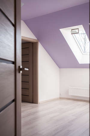 accent: Open door leading to attic room with lilac color accent