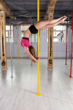 photo studio: Sporty, young pole dancer doing complicated figure
