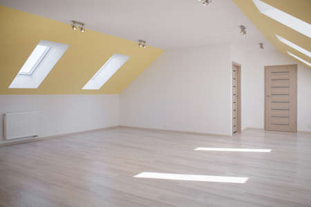 interior designs: Huge empty bright room in the loft of commodious house Stock Photo