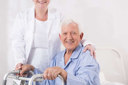 senescence: Photo of happy elderly man with disability and helpful nurse