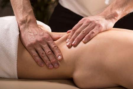 techniek: Jonge vrouw die onderrug ontspannende massage