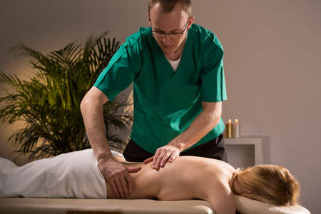 sensual massage: Massage therapist kneading womans lumbar section during spa treatment