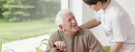 Nurse helping senior man in rest home