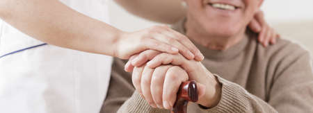 caring: Smiling disabled senior man and caring nurse Stock Photo