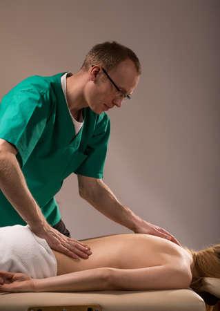 dolor espalda: Masajista realizar masaje de espalda terapéutico de la mujer joven Foto de archivo
