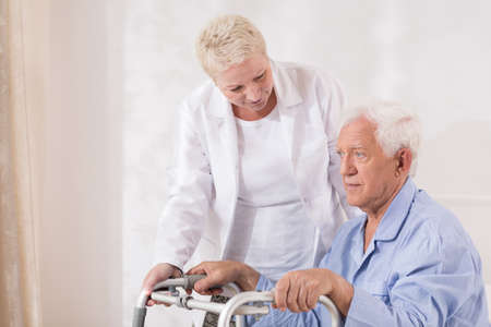 Image of disabled old patient with walking zimmer